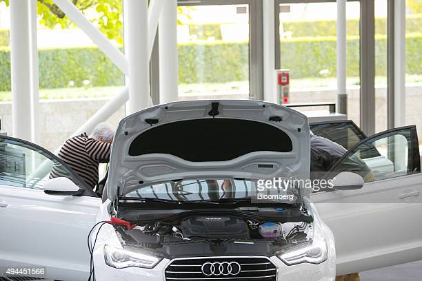 Customers inspect the interior of an Audi A6 automobile manufactured by Volkswagen AG in the Audi Forum at the Audi AG headquarters in Ingolstadt...