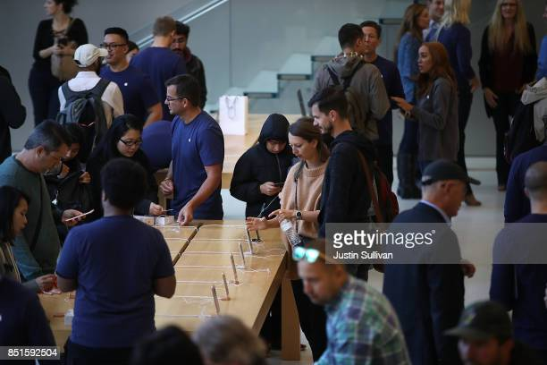 Customers inspect the new Apple iPhone 8 at an Apple Store on September 22 2017 in San Francisco California The new Apple iPhone 8 and 8 Plus as well...