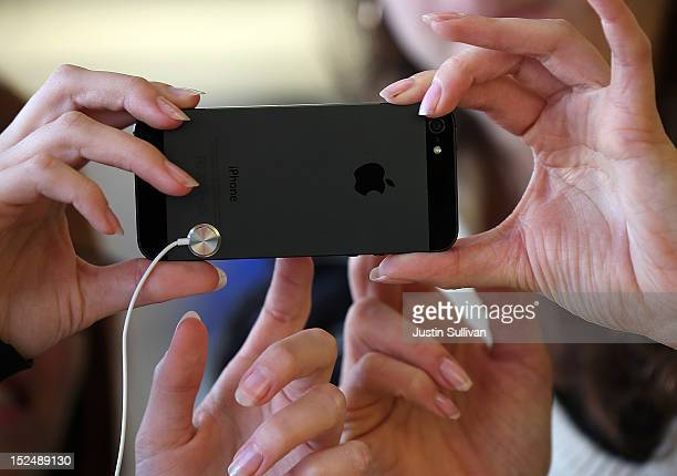 Customers inspect the new iPhone 5 at an Apple Store on September 21 2012 in San Francisco California Customers flocked to Apple Stores across the US...