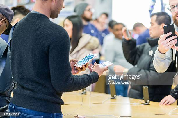 Customers inspect the new iPhone models after the release at the Apple Store in Melbourne Australia on September 16 2016 Apple has released for sale...