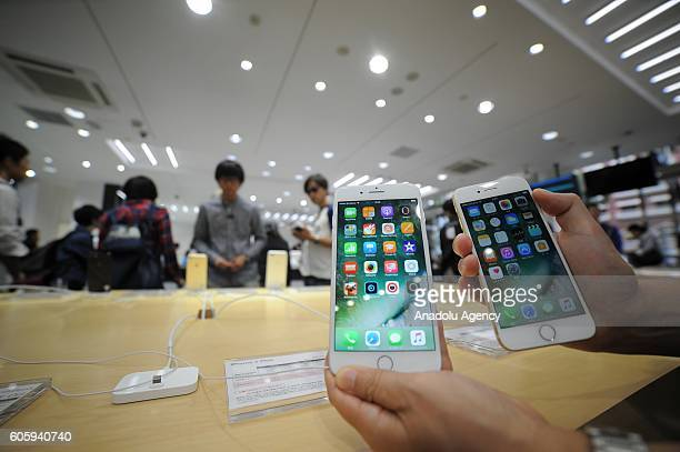 Customers inspects new iPhone models at a telecom shop in Omotesando Avenue in Tokyo Japan on September 16 2016 Apple has released for sale its new...