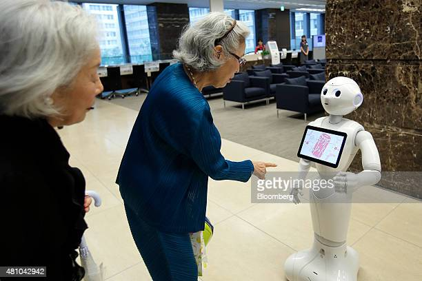 Customers interact with SoftBank Corp's humanoid robot Pepper at a Mizuho Bank Ltd branch in Tokyo Japan on Friday July 17 2015 Mizuho introduced...