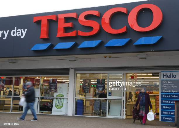 Customers leave a branch of a Tesco supermarket in London on January 27 2017 Britain's biggest retailer Tesco agreed Friday to buy wholesaler Booker...