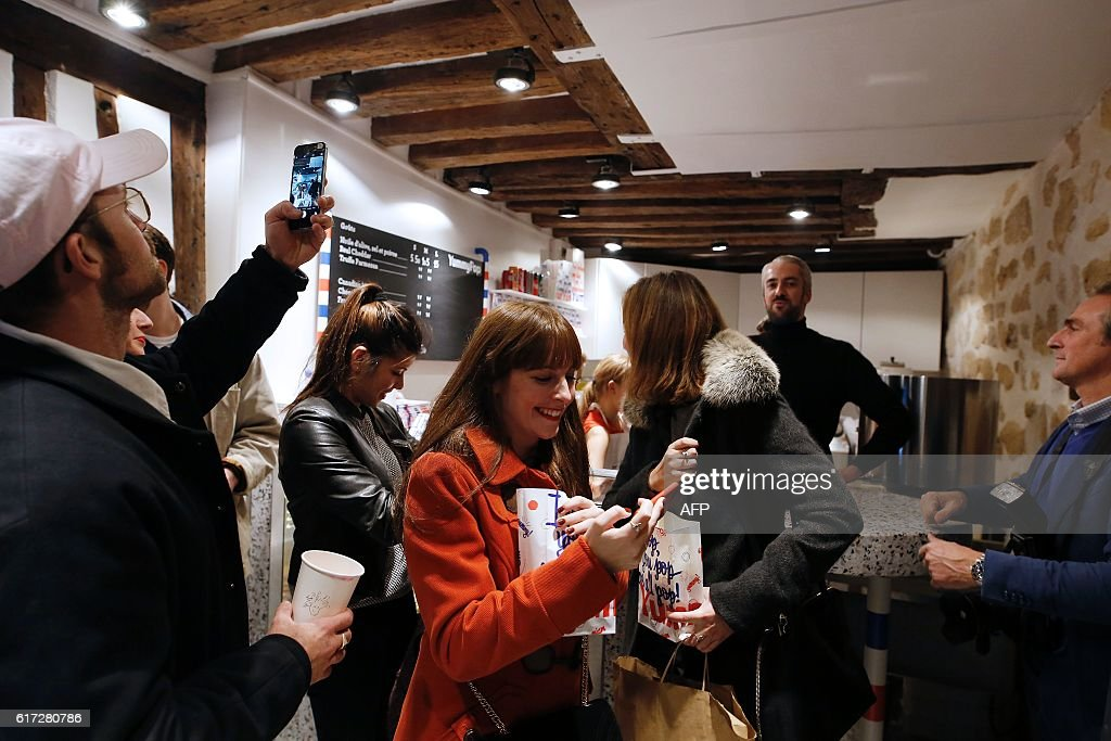 Customers leave after buying popcorn at the opening of the Yummy Pop gourmet popcorn shop in the Marais district of Paris on October 22, 2016. The concept is a labour of love between US actress Scarlett Johansson and her French husband, advertising executive Romain Dauriac. And the couple hope that if their 'Real Vermont Cheddar' and other savoury and sweet recipes are a hit, they will open other shops elsewhere. / AFP / Benjamin CREMEL