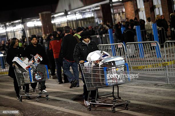 Customers leave WalMart with their purchased items Thanksgiving day on November 28 2013 in Troy Michigan Black Friday shopping began early this year...