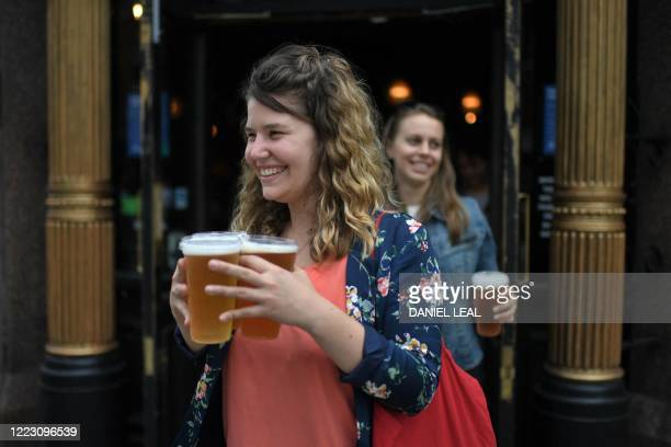Customers leave with pints of beer for takeaway at The Ten Bells pub in east London on June 27, 2020. - The pub serves drinks for takeaway to...