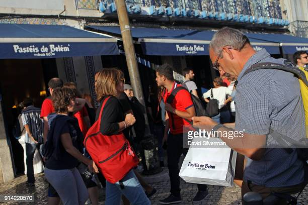 Customers line up on the pavement to shop for takeaway Pastel de nata a traditional Portuguese sweet egg pastry at the famous Pastéis de Belém bakery...