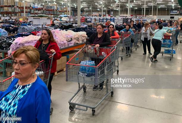 Customers line up to buy water and other supplies on fears that the coronavirus COVID19 will spread and force people to stay indoors at a Costco in...