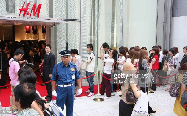 Customers line up to enter the Swedish retailer HM's first store first store in Japan in the highend shopping district Ginza September 13 2007 in...