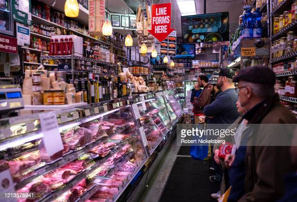 Customers line up to place their orders at Paisanos Butcher Shop in the Brooklyn borough of New York City on March 19, 2020. The coronavirus outbreak...