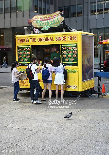 Customers line up to purchase hot dogs and other food items from a Nathan's Famous street vendor set up along a sidewalk in New York City on August...
