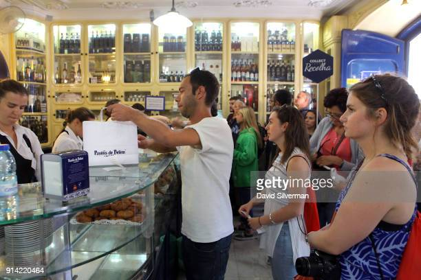 Customers line up to shop for takeaway Pastel de nata a traditional Portuguese sweet egg pastry at the famous Pastéis de Belém bakery and cafe on...