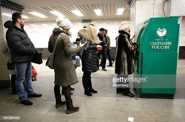Customers line up to withdraw cash from an automated teller machine operated by OAO Sberbank in Moscow Russia on Friday March 22 2013 Russian lenders...