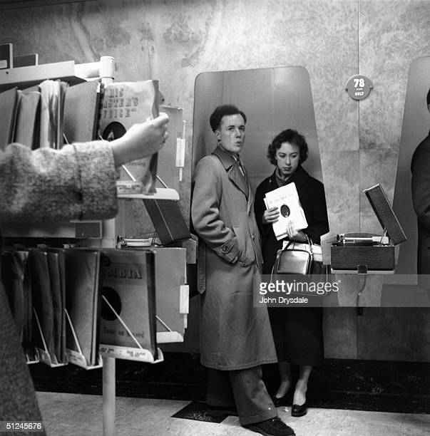Customers listen to the latest record releases at a listening booth in the HMV shop at 363 Oxford Street London 24th November 1955 The records are...