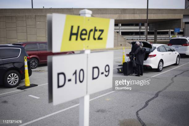 Customers load a vehicle at a Hertz Global Holdings Inc rental location at Louisville International Airport in Louisville Kentucky US on Tuesday Feb...