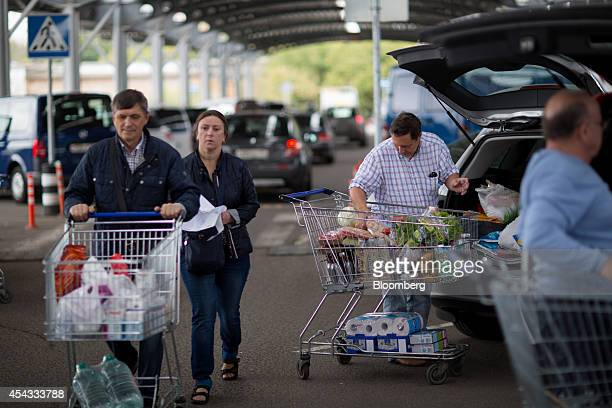 Customers load their vehicles with products after shopping at a Metro Cash Carry store the Russia unit of Metro AG in Moscow Russia on Friday Aug 29...