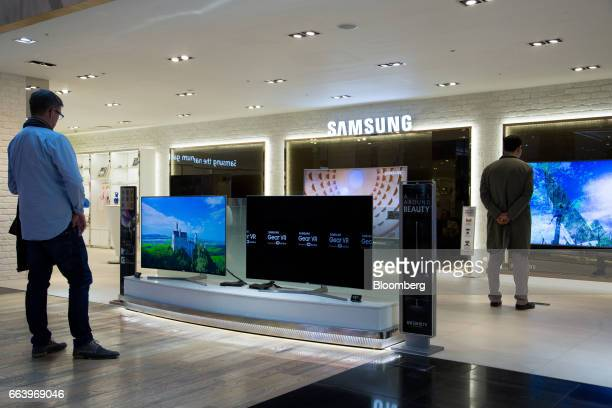 Customers look at a Samsung Electronics Co curved SUHD televisions at the company's D'light flagship store in Seoul South Korea on Monday April 3...