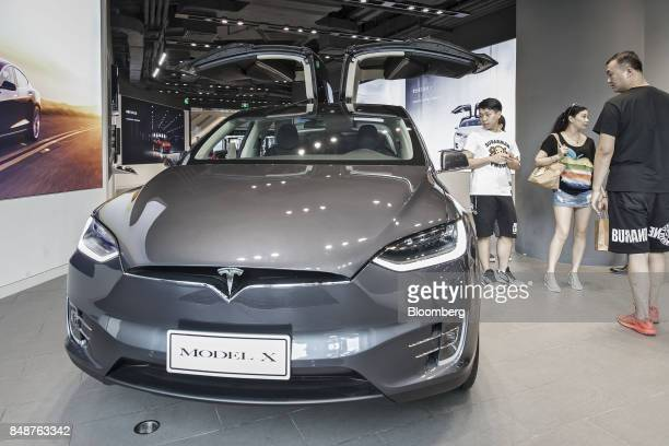 Customers look at a Tesla Motors Inc Model X electric vehicle on display at the company's showroom in Shanghai China on Tuesday Sept 12 2017 China...