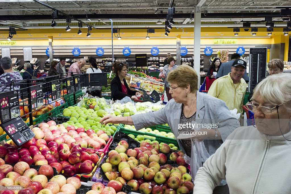 Customers look at apples at the fruits and vegetables section of a Carrefour supermarket, on June 14, 2013 in Sainte-Geneviève-des-Bois, outside Paris. Installed in Sainte-Geneviève-des-Bois since fifty years, on June 15, 1963, this supermarket is the first of French giant retailer Carrefour group, but also the first in France.
