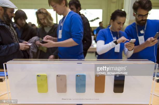 Customers look at Apple's new iPhone 5s smartphones at the Apple Store in Paris on September 20 2013 Apple's new iPhone 5s and 'cheap' 5C models went...