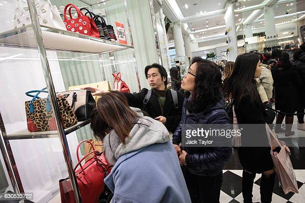 Customers look at cutprice Prada handbags during the Boxing Day sale at Selfridges on December 26 2016 in London England Boxing Day is traditionally...
