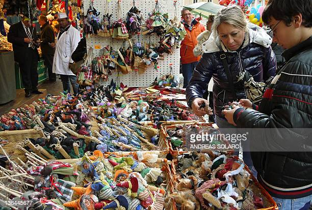 Customers look at dolls of Befana a witch celebrated in Italy on the Christian festival of Epiphany on January 5 2012 at a street seller on Piazza...