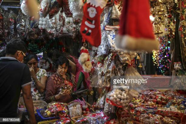 Customers look at festive Christmas decorations at a stall in Mumbai India on Friday Dec 15 2017 India's inflation surged past the central bank's...