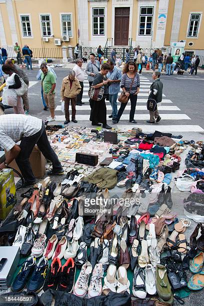 Customers look at footwear and other items for sale at Feira da Ladra flea market in Lisbon Portugal on Saturday Oct 12 2013 Earlier this month...