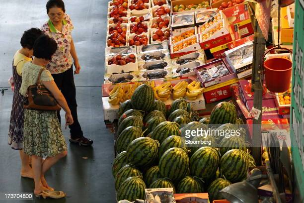 Customers look at fruit at a stall at Noeun Agricultural and Marine Products Wholesale Market in Daejeon, South Korea, on Tuesday, July 16, 2013....