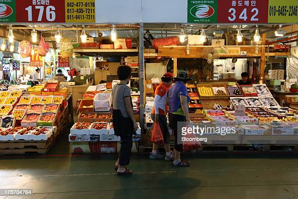 Customers look at fruit at Noeun Agricultural and Marine Products Wholesale Market in Daejeon, South Korea, on Tuesday, July 16, 2013. South Korea...