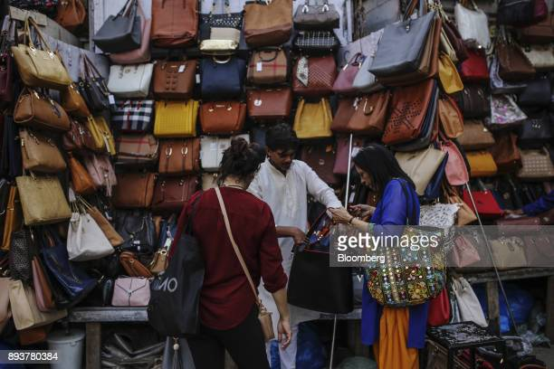 Customers look at handbags at a roadside stall in Mumbai India on Friday Dec 15 2017 India's inflation surged past the central bank's target...