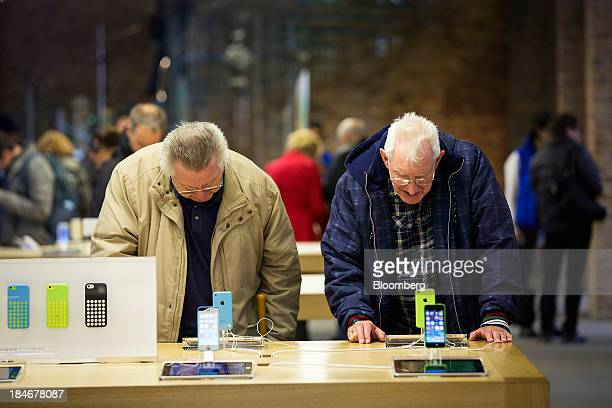 Customers look at iPhone 5C mobile devices as they stand on display inside Apple Inc's Covent Garden store in London UK on Tuesday Oct 15 2013...