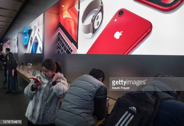 Customers look at iPhones on display at an Apple Store on January 7 2019 in Beijing China Apple Inc lowered its revenue guidance last week blaming...