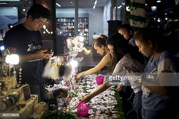 Customers look at jewelry at a market stall in Asiatique The Riverfront openair mall in Bangkok Thailand on Friday Dec 18 2015 Thai economic...