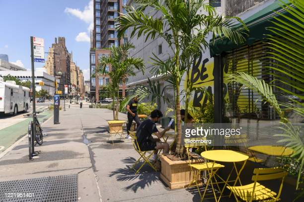 Customers look at menus outside of the Baby Brasa restaurant in the West Village neighborhood of New York, U.S., on Monday, June 22, 2020. No city is...