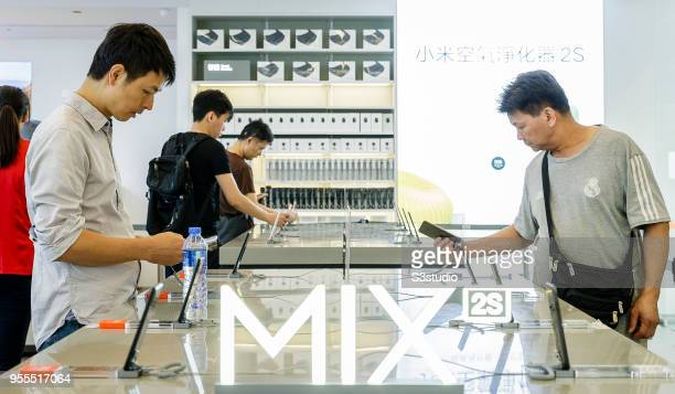 Customers look at Mi MIX 2S smartphones displayed inside of the Xiaomi Corp store on Nathan Road in Hong Kong on May 7 2018 in Hong Kong Hong Kong A...