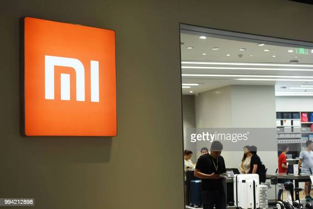 Customers look at products at a Xiaomi store in Hangzhou in China's eastern Zhejiang province on July 9, 2018. - Chinese smartphone giant Xiaomi...