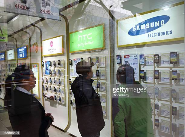 Customers look at Samsung Electronics Co smartphones at a China Mobile Ltd store in Beijing China on Tuesday March 12 2013 China Mobile is scheduled...