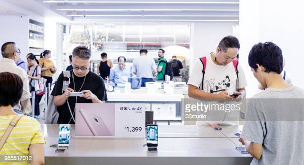 Customers look at smartphones displayed inside of the Xiaomi Corp store on Nathan Road in Hong Kong on May 7 2018 in Hong Kong Hong Kong A report by...