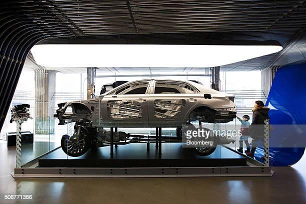 Customers look at the frame and chassis of a Hyundai Motor Co Genesis G90 luxury sedan on display at the Hyundai Motorstudio Seoul showroom in the...