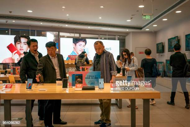 Customers look at Xiaomi smartphones in a shop in Beijing on May 3, 2018. - Chinese smartphone maker Xiaomi has kicked off what is expected to be the...