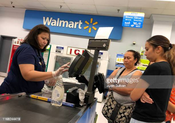 Customers look on as a Walmart cashier rings up their purchases at a Walmart store on August 15, 2019 in Richmond, California. Walmart beat analyst...