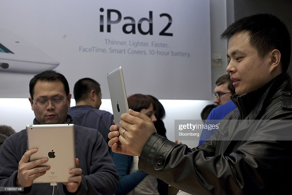 Customers look over Apple Inc.'s iPad 2 at the Apple store in San Francisco, U.S., on Friday, March 11, 2011. Apple may sell 600,000 of the second version of the iPad when it debuts this weekend, extending the device's lead in a crowding market. Photographer: David Paul Morris/Bloomberg via Getty Images