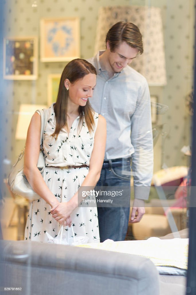 Customers looking at bed in furniture store : Stock Photo