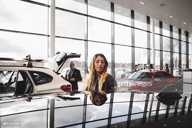 Customers looking at cars in showroom