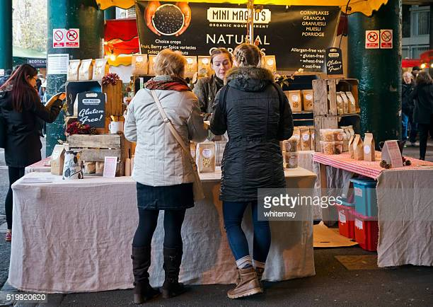 Customers looking at organic foods on a market stall