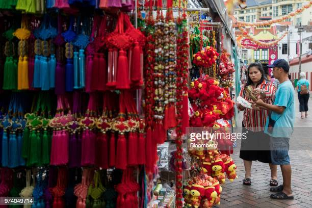 Customers looks at folding fans at a stall in the Chinatown area of Singapore on Wednesday June 13 2018 Tourism as well as the consumer sector will...