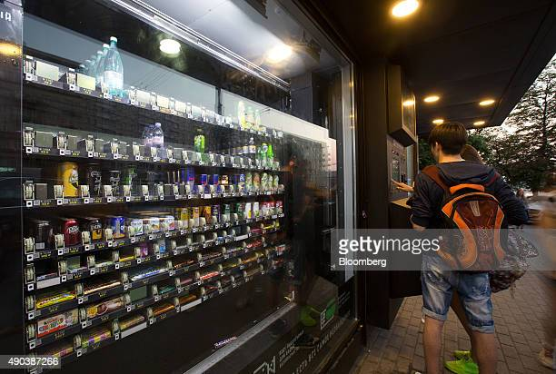 Customers make payment for goods purchased from a Vsyo Sam machine an automated selfservice kiosk on a street in Moscow Russia on Saturday June 13...