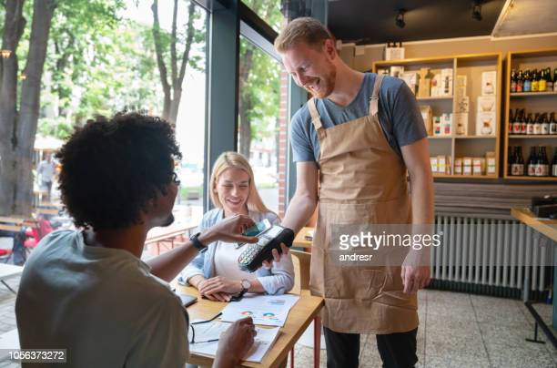 customers making a contactless payment at a restaurant - paying stock pictures, royalty-free photos & images