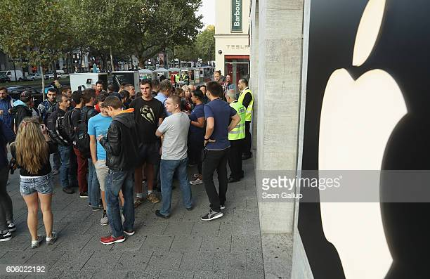 Customers most of whom had preordered the Apple iPhone 7 wait to enter on the first day of sales of the new phone outside the Berlin Apple store on...